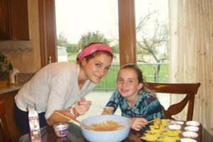Au pair cocinando con su host kid